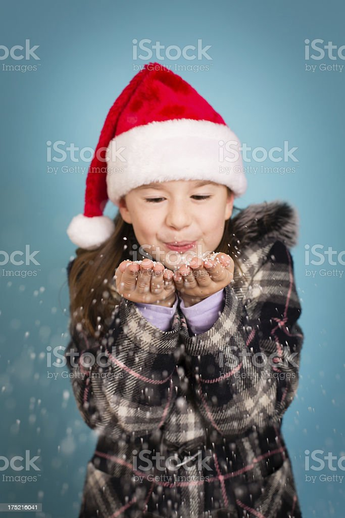Happy Little Girl Blowing Handful of Snow Towards Camera royalty-free stock photo