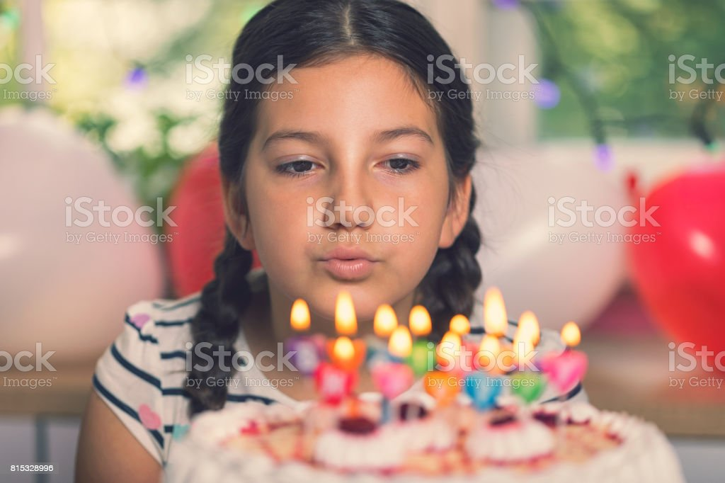 Happy Little Girl Blowing Out Candles On A Birthday Cake