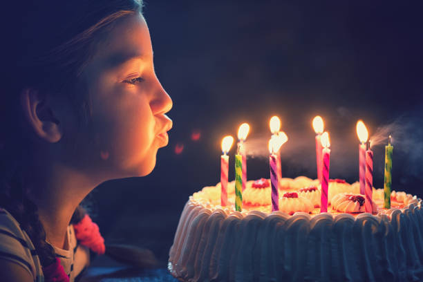 happy little girl blowing out candles on a birthday cake - blowing stock photos and pictures