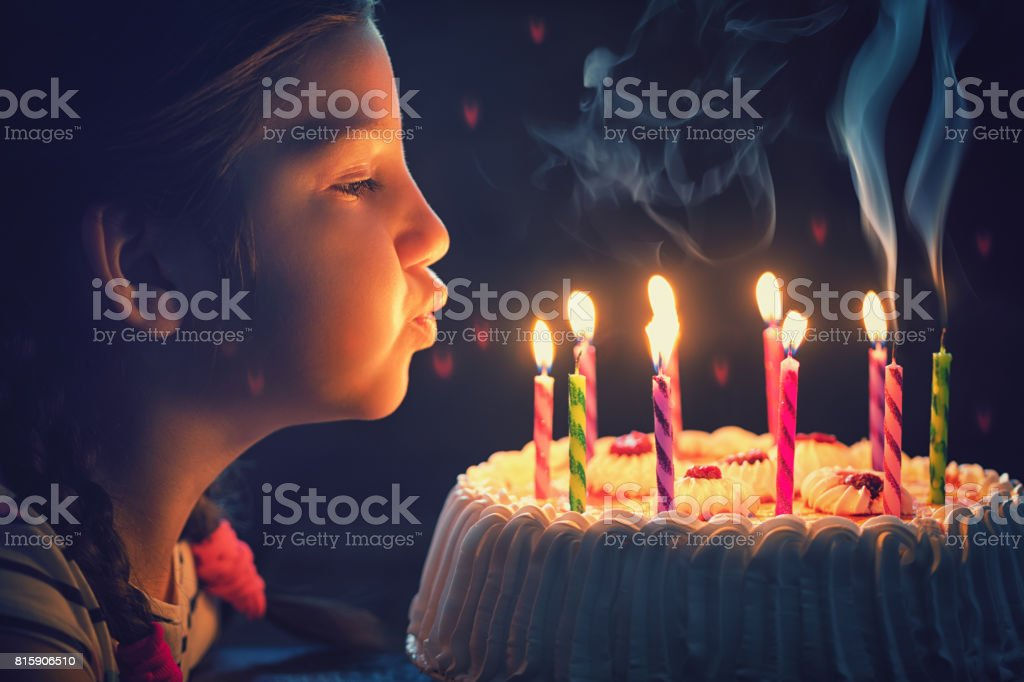Happy little girl blowing out candles on a birthday cake stock photo
