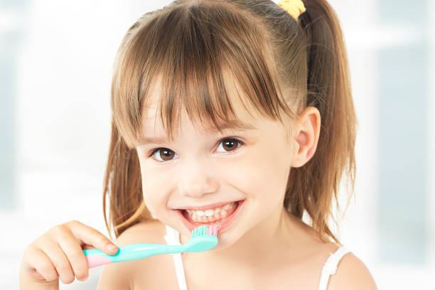 happy little girl brushing her teeth - baby teeth stok fotoğraflar ve resimler