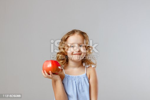 Happy little girl child holding a red apple. Healthy food. Gray background, studio, portrait