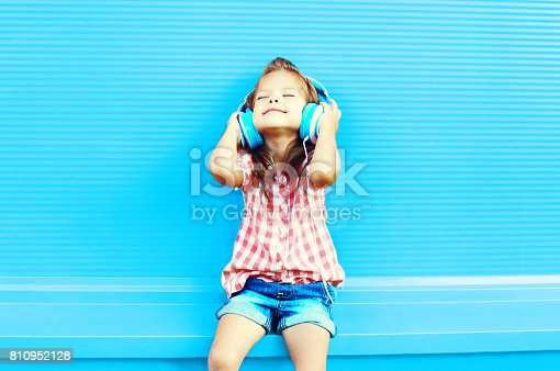 istock Happy little girl child listens to music in headphones on a colorful blue background 810952128