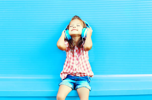 Happy little girl child listens to music in headphones on a colorful blue background stock photo
