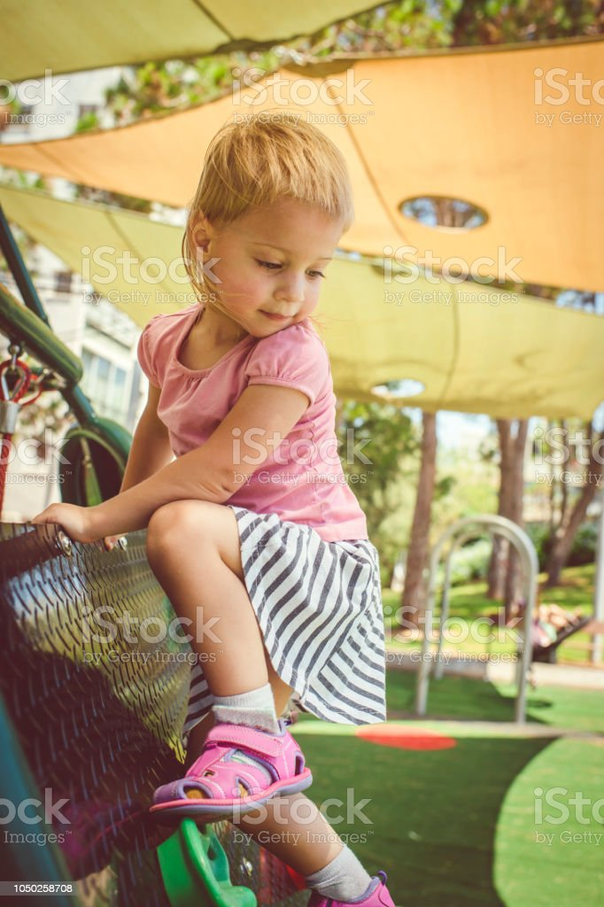 Happy little girl climbing in playground stock photo