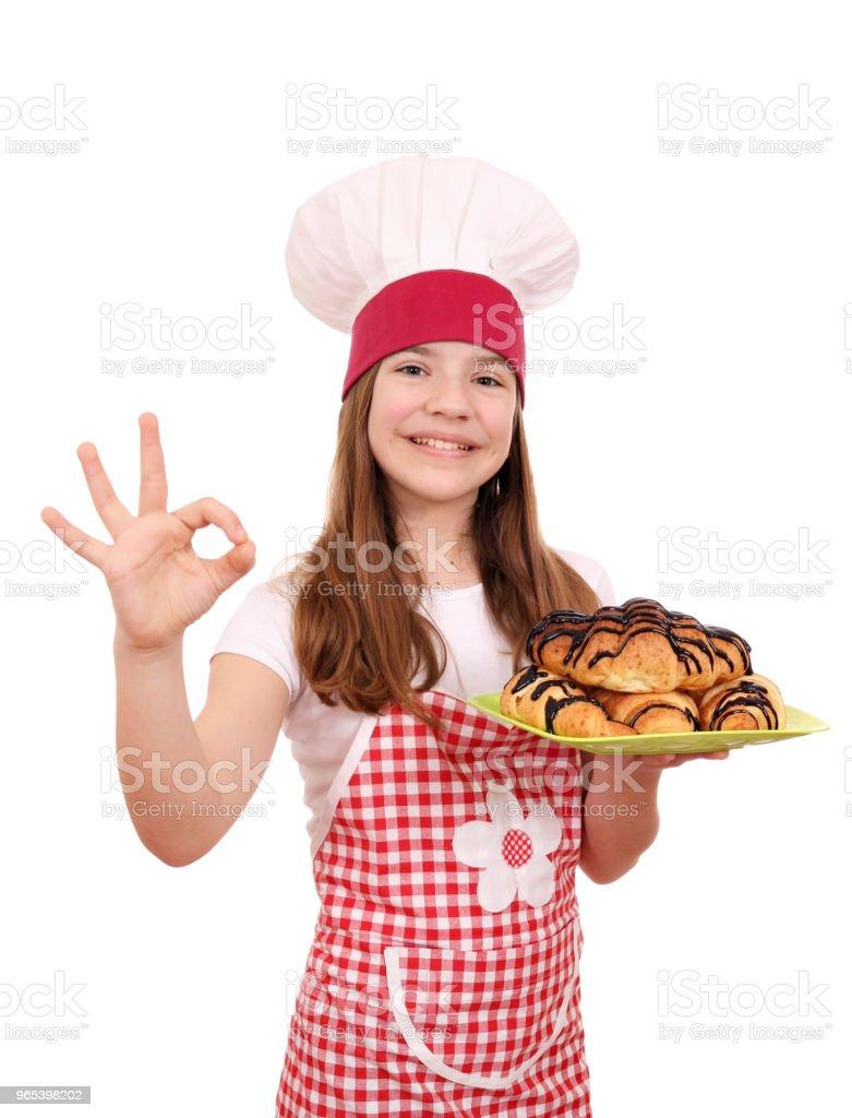 glückliches kleine Mädchen Kochen mit leckeren Croissant und Ordnung Handzeichen - Lizenzfrei Braun Stock-Foto
