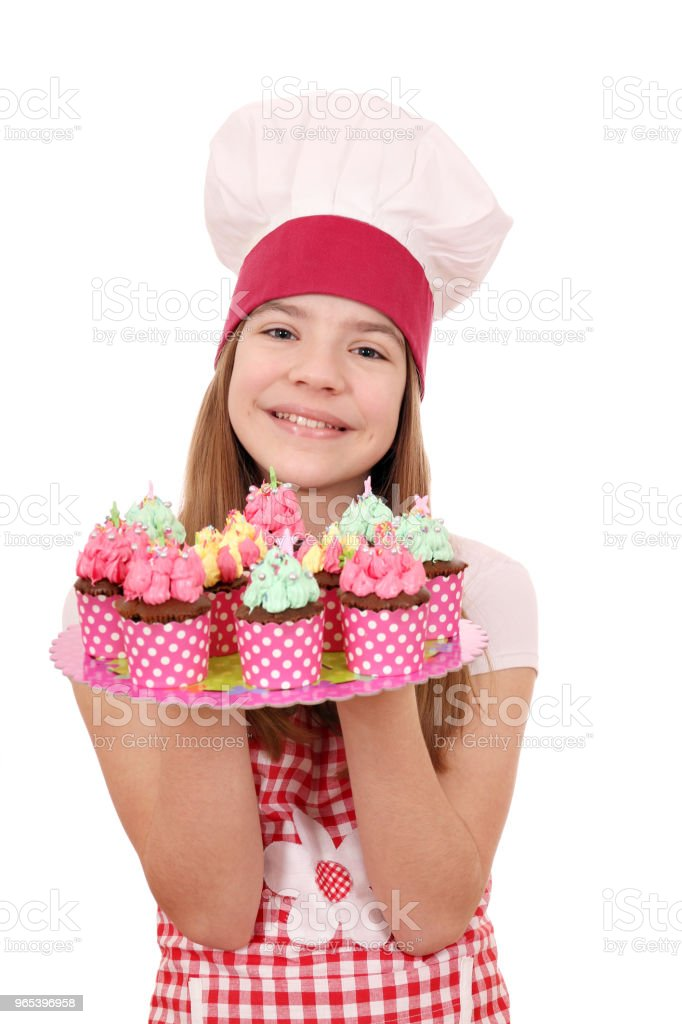 Happy little girl cook with tasty muffins on plate royalty-free stock photo