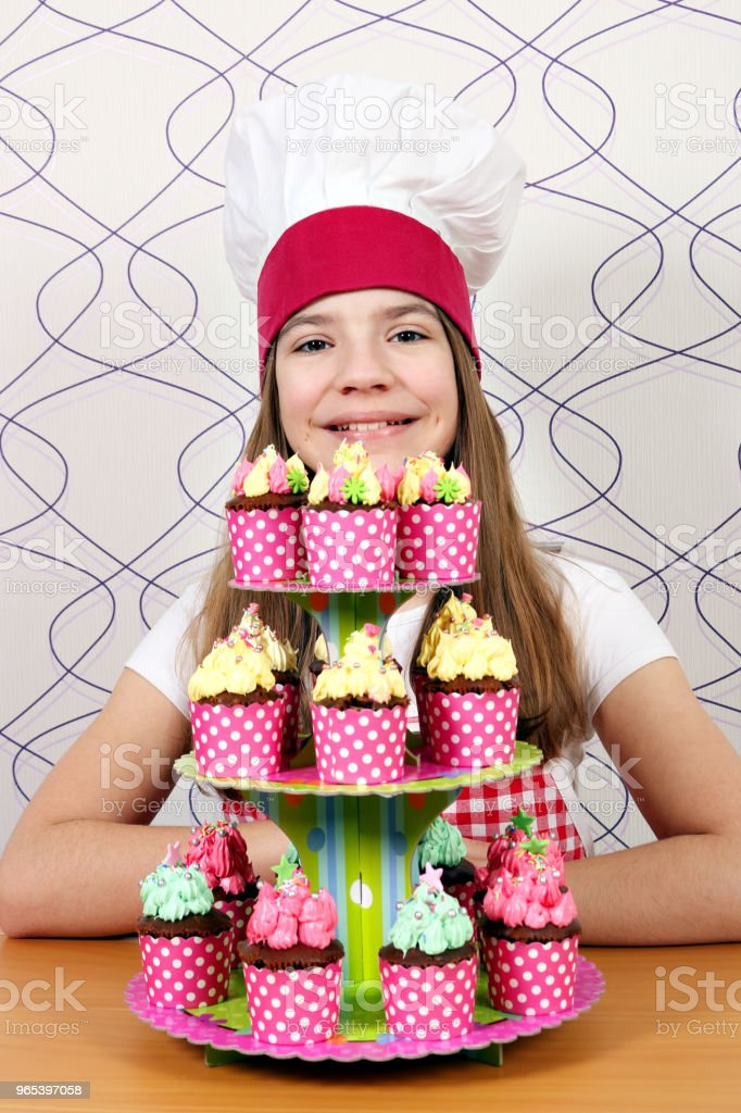 Happy little girl cook with tasty muffins on table zbiór zdjęć royalty-free