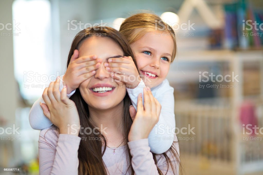 Happy little girl cover her mother eyes stock photo