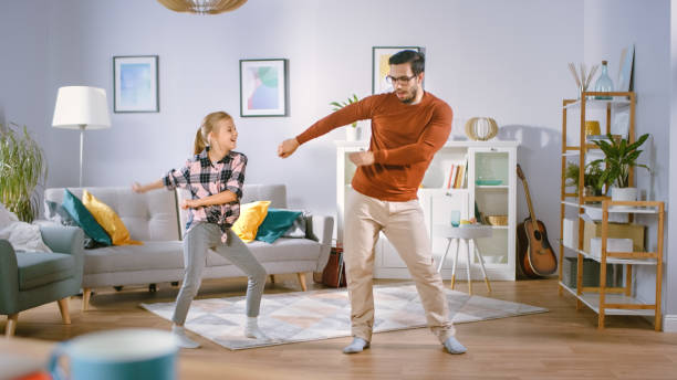 a menina feliz dança com o pai novo no meio da sala de visitas. tempo feliz da família, pai e filha que dançam em casa. - dançar - fotografias e filmes do acervo