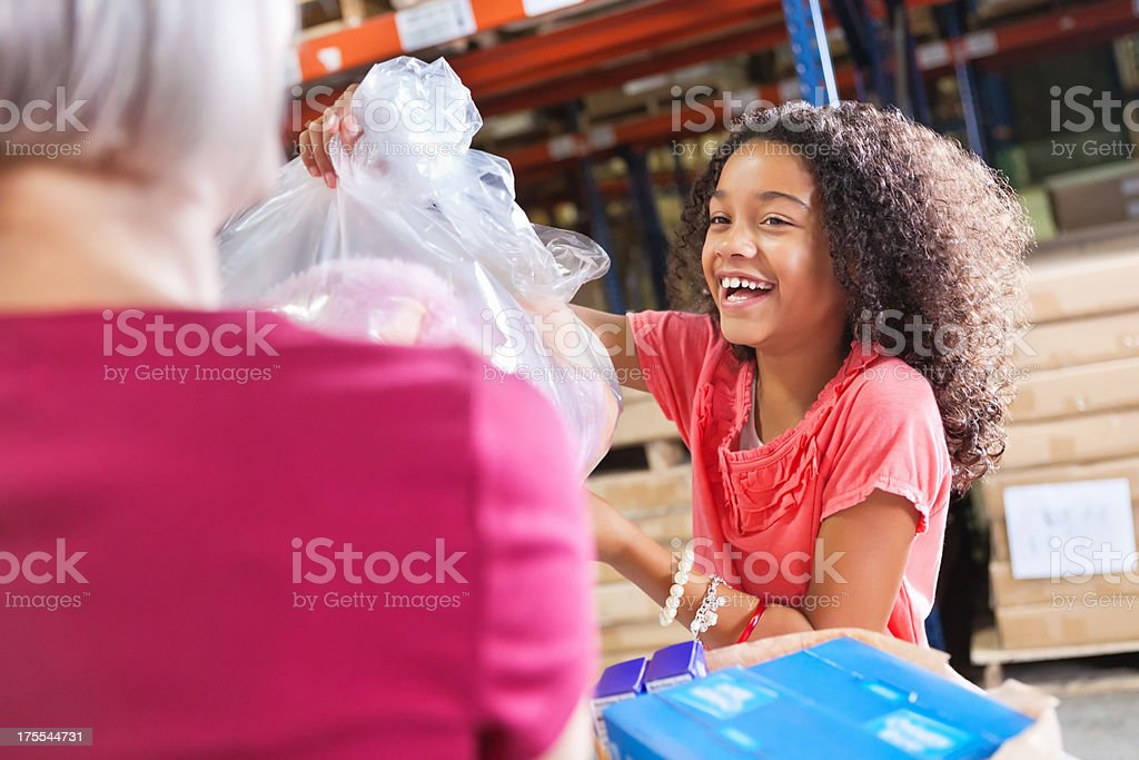Happy little girl donating toys at charity donation drive event stock photo