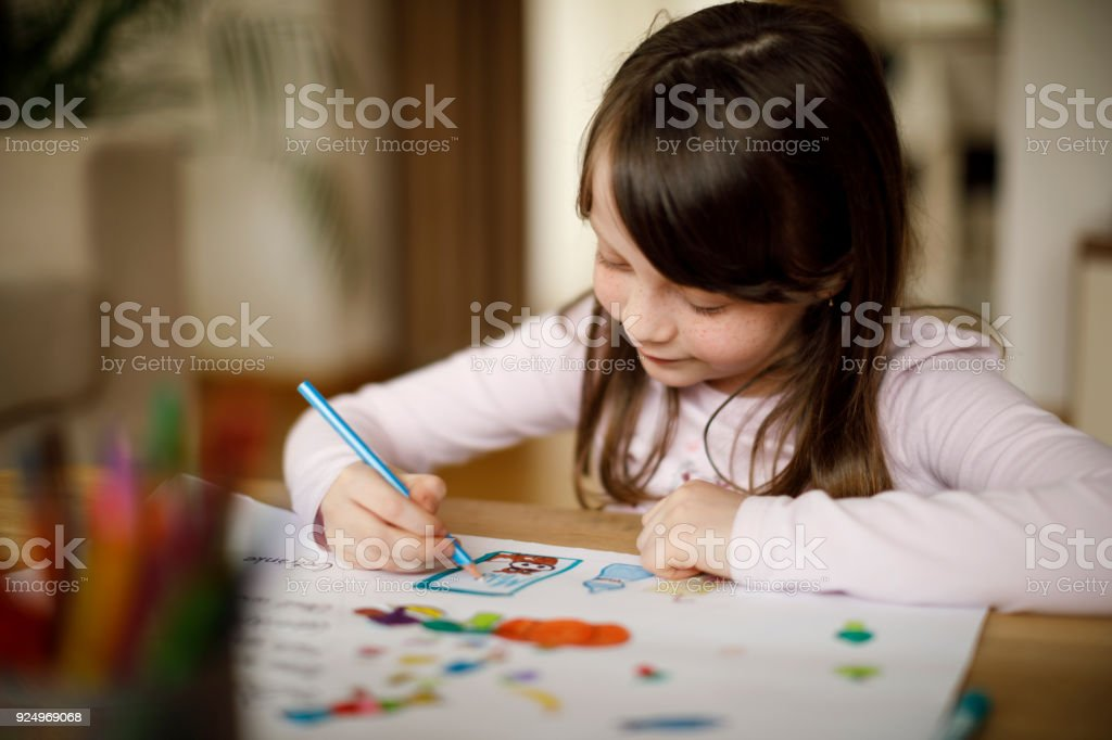 Happy little girl drawing at home stock photo