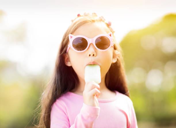gelukkig klein meisje popsicle eten bij zomer - ijslollie bevroren zoetigheid stockfoto's en -beelden