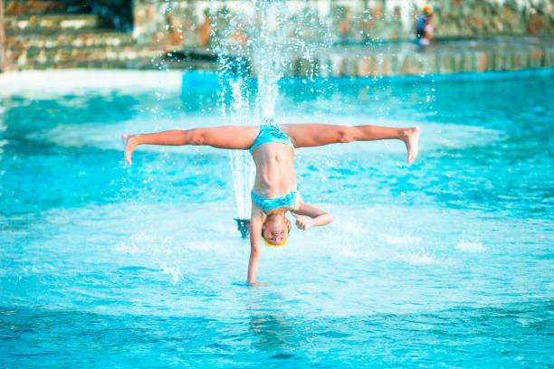 glückliches kleine mädchen genießen sie urlaub im schwimmbad. sportliches kind machen wagenrad am rande des pools - sonnenbrille kleinkind stock-fotos und bilder