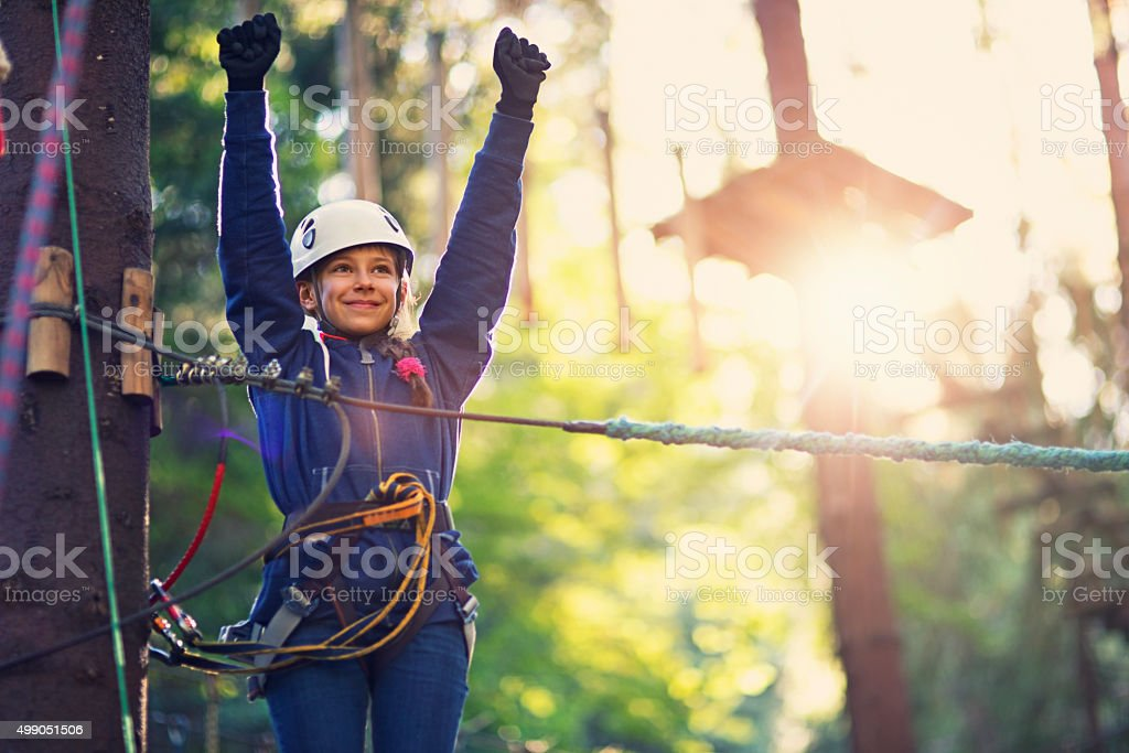 Happy little girl enjoying ropes course adventure park stock photo
