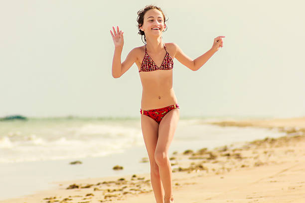 happy little girl enjoying vacations on deserted beach - petites filles photos et images de collection