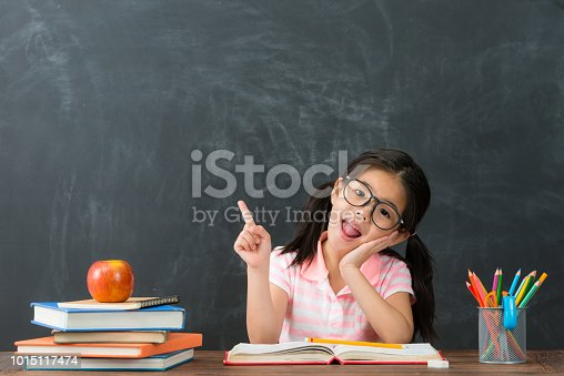 happy attractive little girl face to camera pointing air having good idea when she back to school studying in chalkboard background.