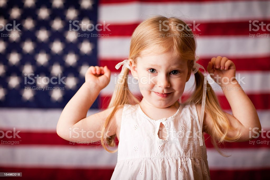Happy Little Girl Flexing in Front of American Flag royalty-free stock photo