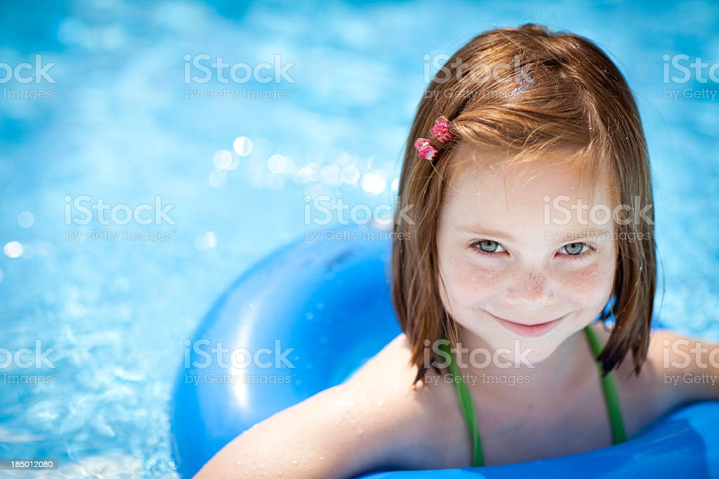 Happy Little Girl Floating With Swim Ring in Swimming Pool royalty-free stock photo