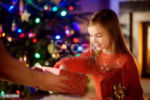 1061876006istockphoto Happy little girl getting a Christmas gift from her parent 628023858