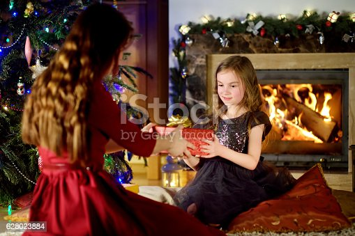 1061876006istockphoto Happy little girl getting a Christmas gift from her parent 628023884
