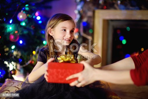 1061876006istockphoto Happy little girl getting a Christmas gift from her parent 628023898