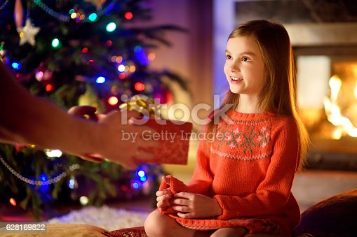 1061876006istockphoto Happy little girl getting a Christmas gift from her parent 628169822