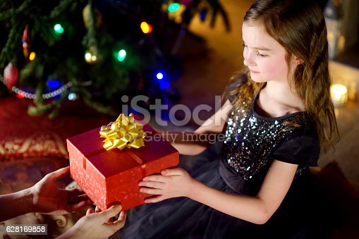 1061876006istockphoto Happy little girl getting a Christmas gift from her parent 628169858
