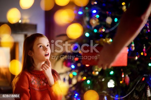 1061876006istockphoto Happy little girl getting a Christmas gift from her parent 628418864