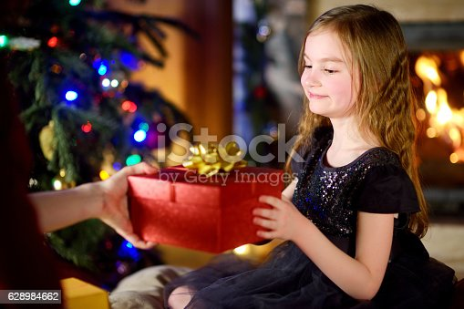 1061876006istockphoto Happy little girl getting a Christmas gift from her parent 628984662