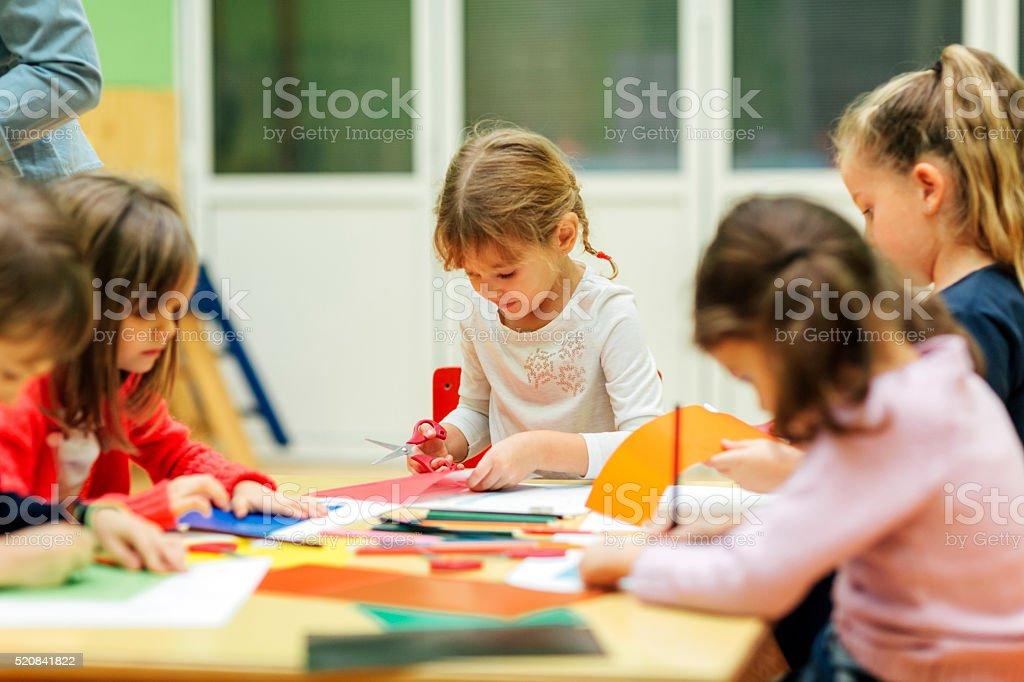 Happy Little Girl Having Creative Activity in kindergarten. stock photo