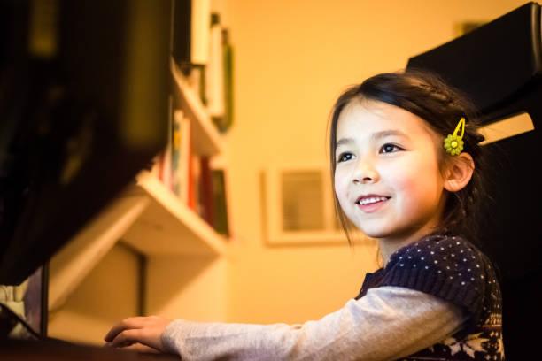 happy little girl having fun using a computer at home - lernfortschrittskontrolle stock-fotos und bilder