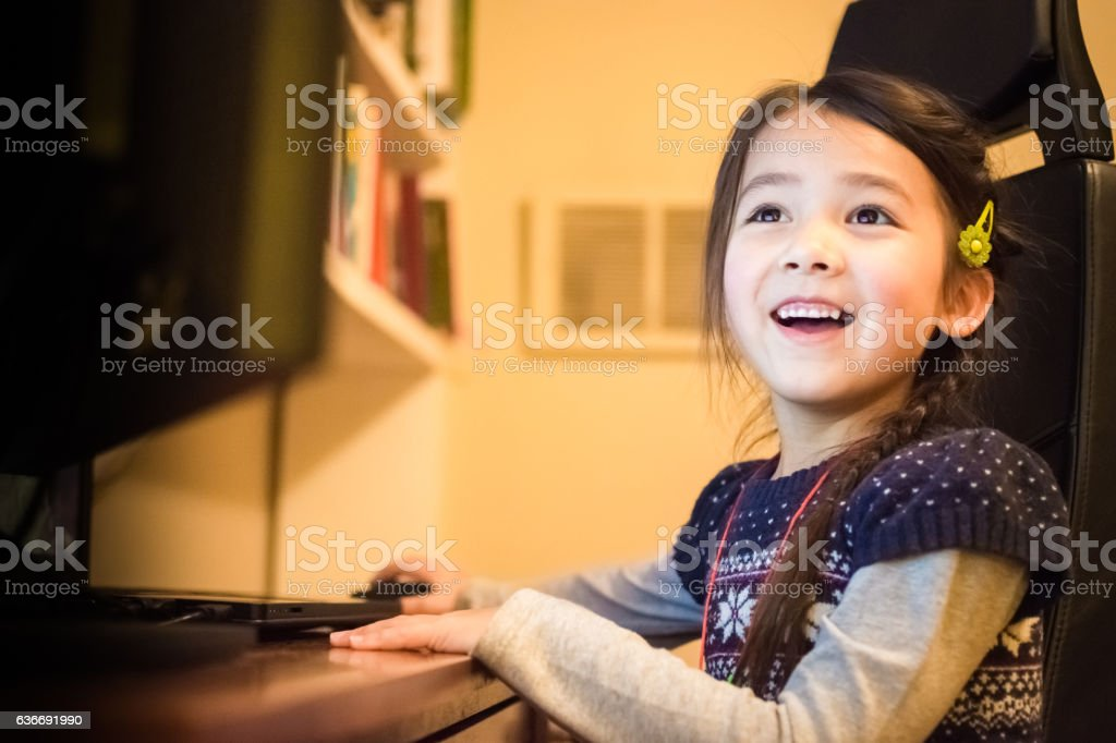 Happy little girl having fun using a computer at home stock photo