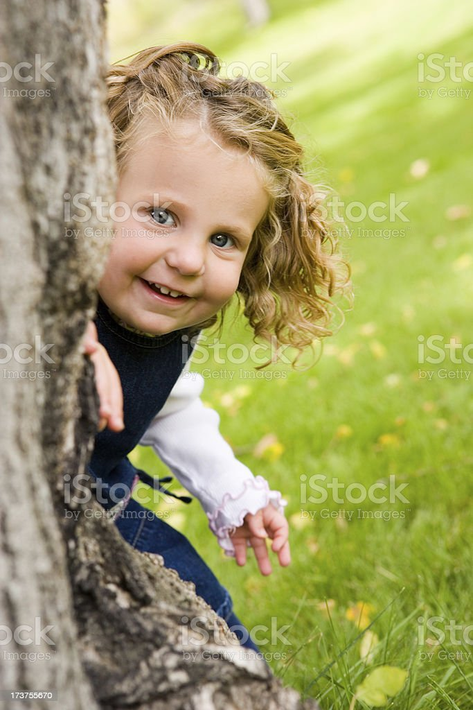 Happy Little Girl Hiding Behind Tree royalty-free stock photo