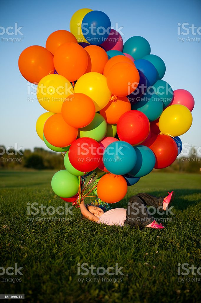 Happy Little Girl Holding a Bunch of Balloons Outside royalty-free stock photo