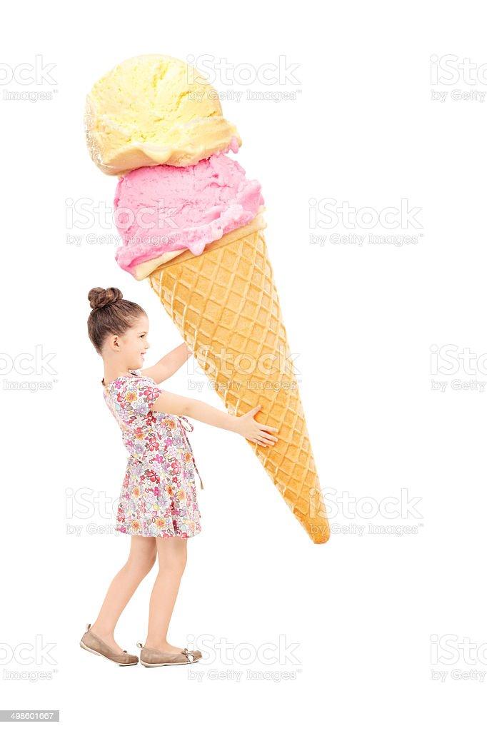 Happy little girl holding a huge ice cream stock photo