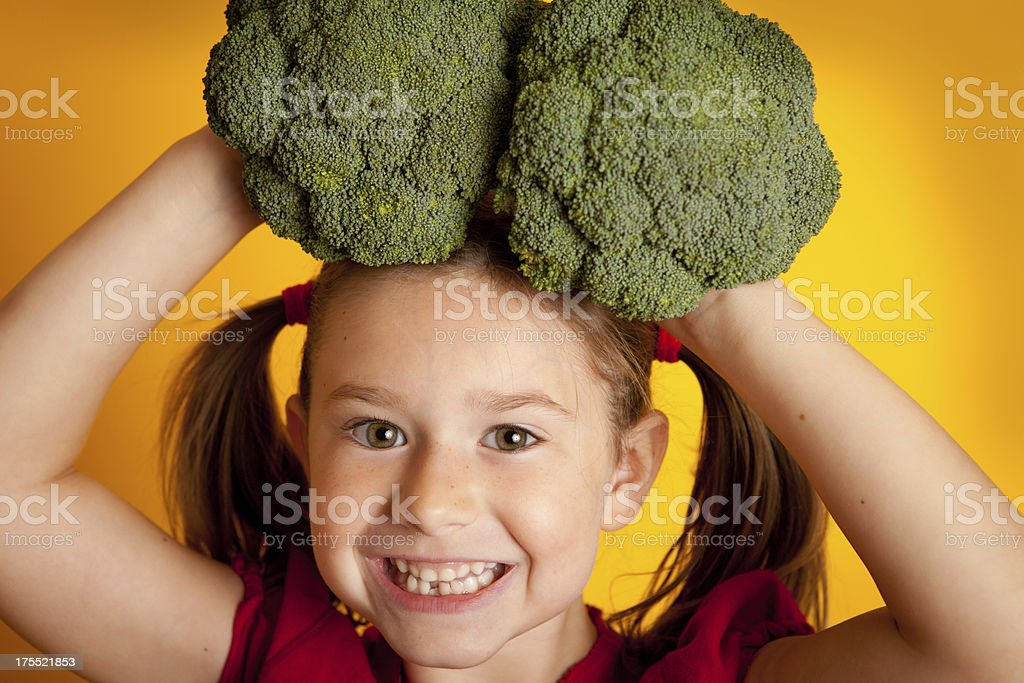 Happy Little Girl Holding Broccoli on Her Head royalty-free stock photo