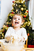 Happy little girl holding dough and laughing at flour falling, in front of a christmas tree