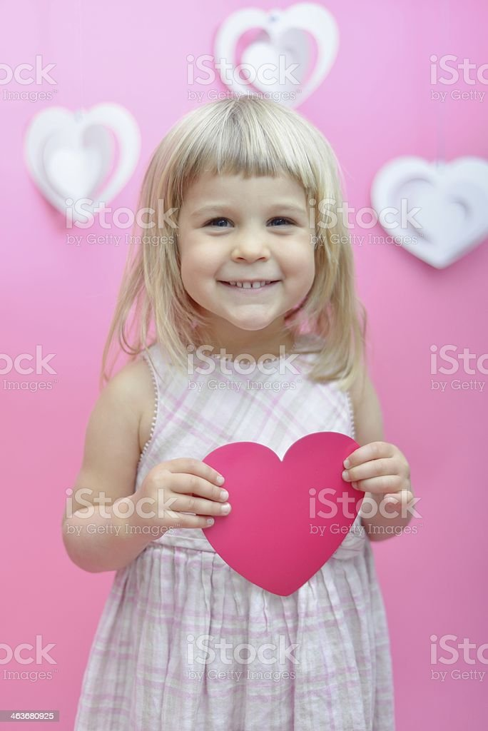 Happy little girl holding heart shaped card stock photo