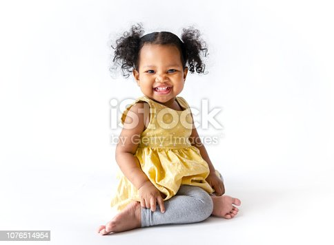 istock Happy little girl in a yellow dress sitting 1076514954