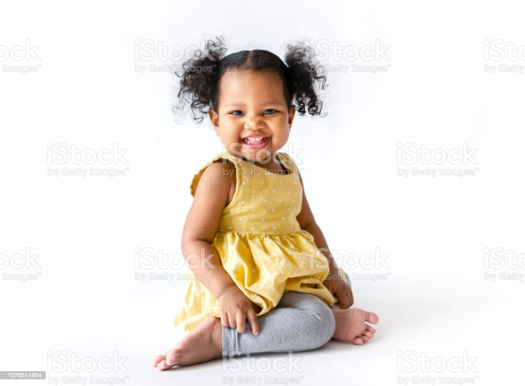 Happy little girl in a yellow dress sitting stock photo