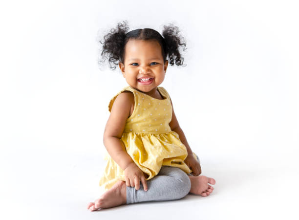 Happy little girl in a yellow dress sitting - foto stock