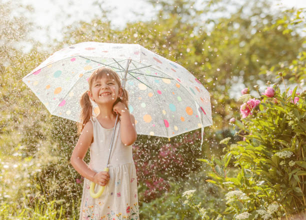 Happy little girl in garden under the summer rain with an umbrella. stock photo