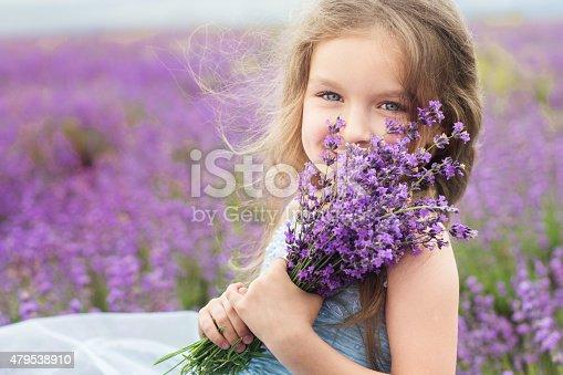 Portrait of happy little girl is in a lavender field holding bouquet of flowers