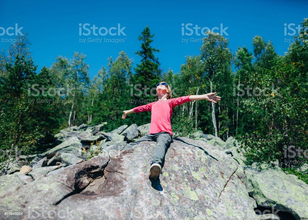 Glückliche kleine Mädchen in den Bergen mit Handzeichen zur Sonne – Foto