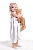 Little girl wearing white dress smiling on white background hugging a toy.
