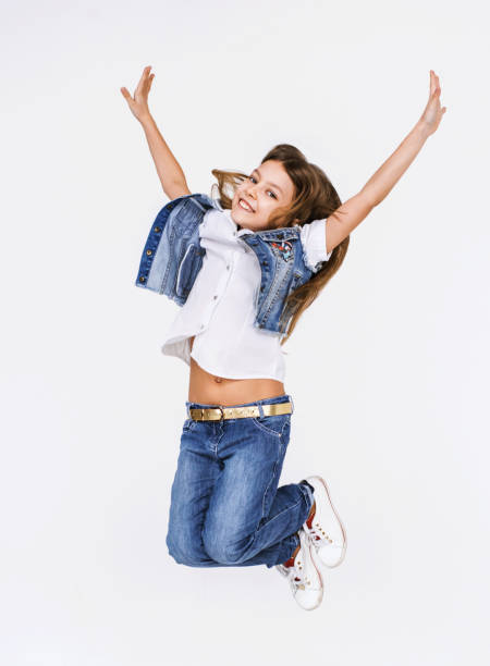 Happy little girl jumping and having fun stock photo