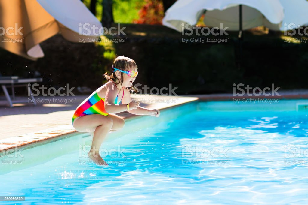 Happy little girl jumping into swimming pool stock photo