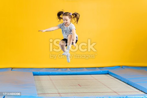 Happy child girl jumping on trampoline in fitness center