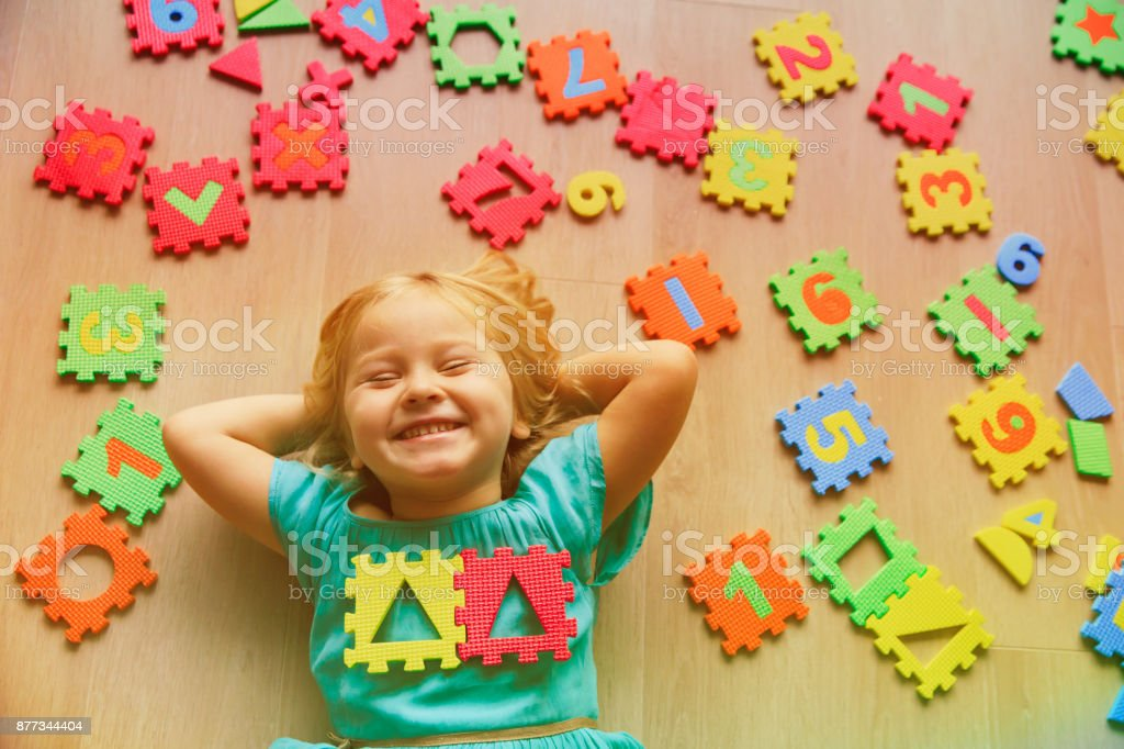 happy little girl learn numbers and shapes, play with puzzle royalty-free stock photo